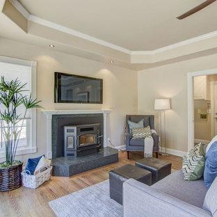 Foto de sala de estar abierta, clásica, pequeña, con paredes beige, suelo de madera en tonos medios, estufa de leña, marco de chimenea de baldosas y/o azulejos, televisor colgado en la pared y suelo multicolor