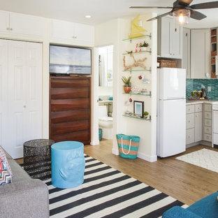 サンディエゴの小さいビーチスタイルのおしゃれなファミリールーム (白い壁、クッションフロア、壁掛け型テレビ、茶色い床) の写真