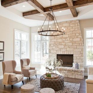 Modelo de sala de estar abierta, campestre, de tamaño medio, sin televisor, con paredes beige, chimenea tradicional, marco de chimenea de piedra, suelo marrón y suelo de madera oscura