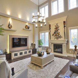 Cette photo montre une salle de séjour chic ouverte et de taille moyenne avec un mur beige, un sol en bois foncé, une cheminée standard, un téléviseur fixé au mur, un manteau de cheminée en bois et un sol beige.