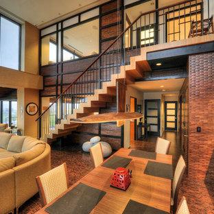 Cette photo montre une salle de séjour tendance de taille moyenne et ouverte avec un mur beige, un sol en liège, aucune cheminée, un téléviseur dissimulé et un sol marron.