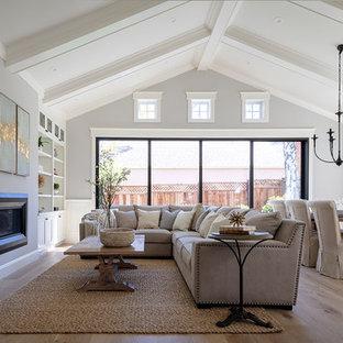 Diseño de sala de estar abierta, campestre, pequeña, con paredes grises, suelo de madera clara, chimenea de doble cara, marco de chimenea de yeso, televisor colgado en la pared y suelo gris
