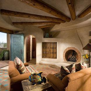 Aménagement d'une salle de séjour sud-ouest américain fermée avec un mur beige, un sol en carreau de terre cuite, une cheminée standard, un manteau de cheminée en brique et un sol multicolore.