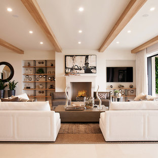 Tuscan open concept limestone floor and beige floor family room photo in Orange County with white walls, a wall-mounted tv and a standard fireplace