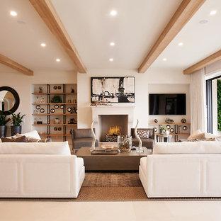 オレンジカウンティの地中海スタイルのおしゃれなオープンリビング (白い壁、ライムストーンの床、壁掛け型テレビ、標準型暖炉、ベージュの床) の写真