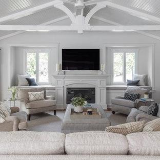 サンフランシスコの大きいトラディショナルスタイルのおしゃれなファミリールーム (無垢フローリング、標準型暖炉、木材の暖炉まわり、壁掛け型テレビ、茶色い床、白い壁) の写真