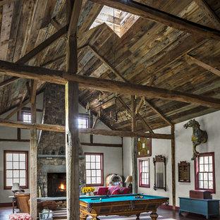 Modelo de sala de juegos en casa campestre, extra grande, con paredes blancas, suelo de madera oscura, chimenea tradicional y marco de chimenea de piedra