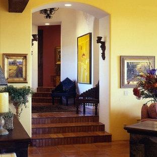 フェニックスの中くらいのサンタフェスタイルのおしゃれなオープンリビング (ゲームルーム、黄色い壁、テラコッタタイルの床) の写真