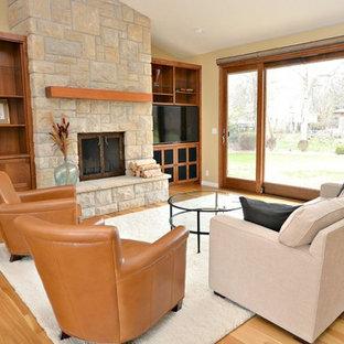 Idées déco pour une salle de séjour craftsman de taille moyenne avec un sol en bois clair, une cheminée standard, un manteau de cheminée en pierre et un téléviseur indépendant.
