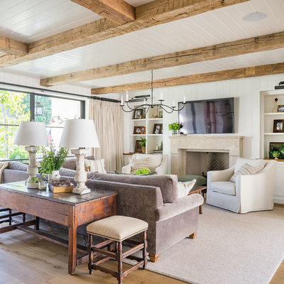 Family room - coastal light wood floor family room idea in Orange County with white walls, a standard fireplace and a wall-mounted tv