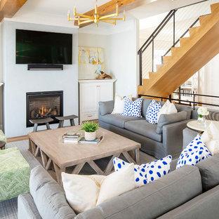 Diseño de sala de estar abierta, marinera, grande, con chimenea tradicional, televisor colgado en la pared, paredes blancas, suelo de madera clara, marco de chimenea de hormigón y suelo marrón
