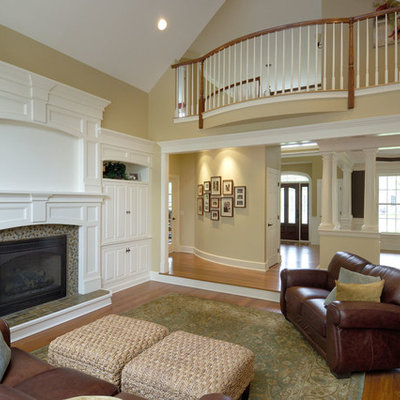 Inspiration for a mid-sized timeless enclosed medium tone wood floor family room remodel in Boston with no tv, yellow walls, a standard fireplace and a tile fireplace