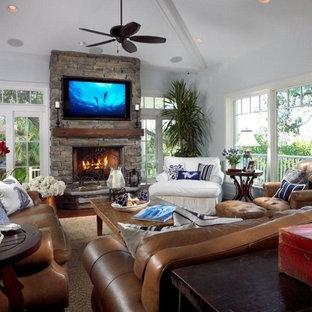 マイアミの大きいビーチスタイルのおしゃれなファミリールーム (グレーの壁、濃色無垢フローリング、標準型暖炉、石材の暖炉まわり、壁掛け型テレビ、茶色い床) の写真