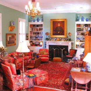Foto di un grande soggiorno tradizionale chiuso con libreria, pareti verdi, pavimento in legno massello medio, camino classico e cornice del camino in legno