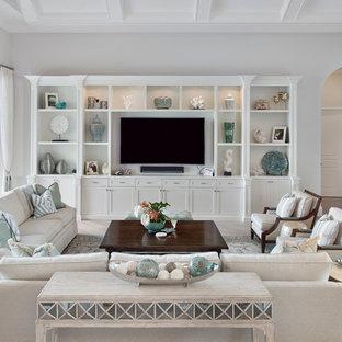 Imagen de sala de estar abierta, clásica, grande, sin chimenea, con suelo de madera clara y televisor colgado en la pared