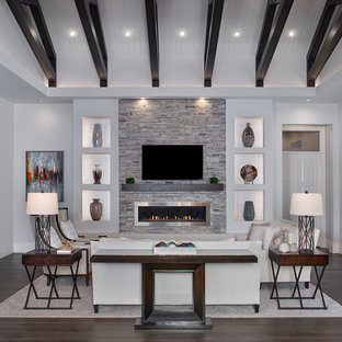 Large transitional open concept dark wood floor and brown floor family room photo in Miami with gray walls, a ribbon fireplace, a metal fireplace and a wall-mounted tv