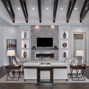 Foto de sala de estar abierta, tradicional renovada, grande, con paredes grises, suelo de madera oscura, chimenea lineal, marco de chimenea de metal, televisor colgado en la pared y suelo marrón