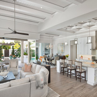 Large transitional open concept light wood floor family room photo in Miami with gray walls, no fireplace and a wall-mounted tv