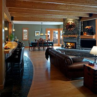 Cette image montre une salle de séjour design de taille moyenne et ouverte avec une cheminée d'angle, un manteau de cheminée en pierre, un bar de salon, un mur vert, un sol en bois clair et un téléviseur fixé au mur.