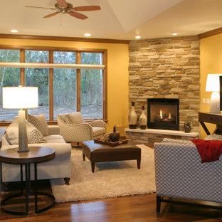 Aménagement d'une grande salle de séjour classique ouverte avec un mur jaune, un sol en bois foncé, une cheminée d'angle, un manteau de cheminée en pierre, un téléviseur indépendant et un sol marron.