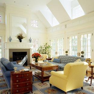 Foto de sala de estar tradicional con paredes beige, suelo de madera en tonos medios y chimenea tradicional