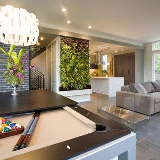 Diseño de sala de juegos en casa abierta, contemporánea, con paredes beige, chimenea de doble cara, suelo gris y suelo de madera oscura