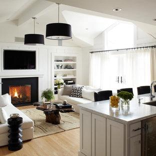 Modelo de sala de estar abierta, tradicional renovada, con paredes blancas, chimenea tradicional, televisor colgado en la pared y suelo de madera clara