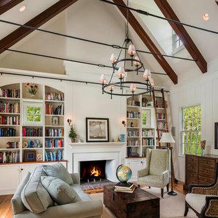 Modelo de sala de estar con biblioteca de estilo de casa de campo, sin televisor, con paredes blancas, suelo de madera en tonos medios, chimenea tradicional y marco de chimenea de yeso