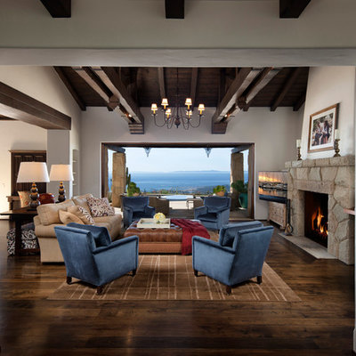 Example of a tuscan dark wood floor family room design in Santa Barbara with white walls, a standard fireplace and a stone fireplace