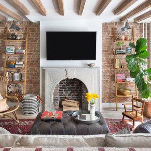 Imagen de sala de estar cerrada, clásica renovada, de tamaño medio, con chimenea tradicional, televisor colgado en la pared, paredes multicolor, suelo de madera clara, marco de chimenea de piedra y suelo beige