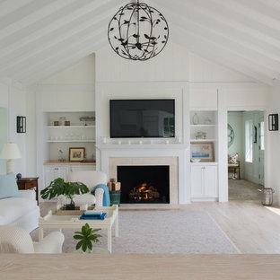 Aménagement d'une grande salle de séjour campagne fermée avec un mur blanc, un sol en contreplaqué, une cheminée standard, un manteau de cheminée en carrelage, un téléviseur fixé au mur et un sol marron.