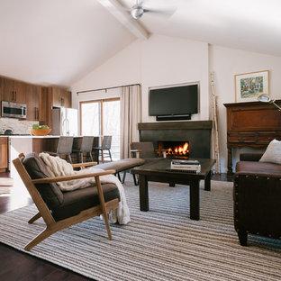 ニューヨークの中くらいのコンテンポラリースタイルのおしゃれなオープンリビング (白い壁、濃色無垢フローリング、標準型暖炉、コンクリートの暖炉まわり、壁掛け型テレビ、茶色い床) の写真