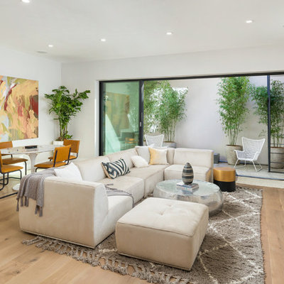 Inspiration for a mid-sized contemporary enclosed light wood floor and beige floor family room remodel in San Francisco with white walls, a wall-mounted tv and no fireplace