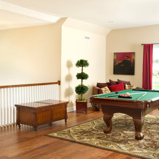 Example of a mid-sized arts and crafts loft-style medium tone wood floor game room design in Other with beige walls, no fireplace and no tv