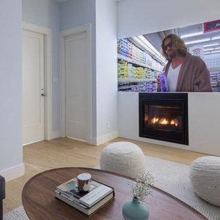 ニューヨークの小さいモダンスタイルのおしゃれな独立型ファミリールーム (青い壁、淡色無垢フローリング、標準型暖炉、壁掛け型テレビ、茶色い床) の写真