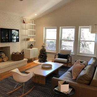 デンバーの中サイズのミッドセンチュリースタイルのおしゃれな独立型ファミリールーム (ベージュの壁、無垢フローリング、標準型暖炉、レンガの暖炉まわり、壁掛け型テレビ、茶色い床) の写真