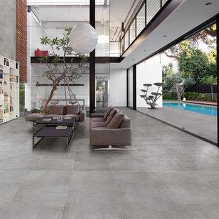 Idee per un ampio soggiorno industriale aperto con libreria, pareti grigie, pavimento in gres porcellanato e TV a parete