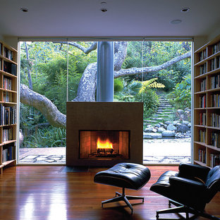 Mid-sized minimalist medium tone wood floor family room library photo in Los Angeles with a standard fireplace, a plaster fireplace and a media wall
