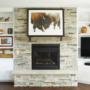 Kleines, Offenes Landhausstil Wohnzimmer mit grauer Wandfarbe, dunklem Holzboden, Kamin, Kaminumrandung aus Stein, Eck-TV und braunem Boden in Sonstige
