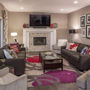 Aménagement d'une salle de séjour classique de taille moyenne et fermée avec un mur gris, un sol en bois foncé, une cheminée standard, un manteau de cheminée en carrelage, un téléviseur fixé au mur et un sol gris.