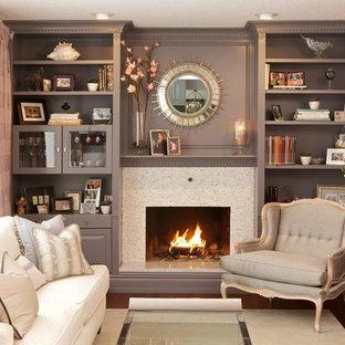 Modelo de sala de estar clásica con suelo de madera oscura, chimenea tradicional, marco de chimenea de piedra y paredes rosas