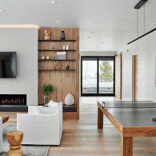 Modelo de sala de juegos en casa abierta, actual, grande, con paredes blancas, suelo de madera clara, chimenea lineal, televisor colgado en la pared, suelo beige y marco de chimenea de yeso