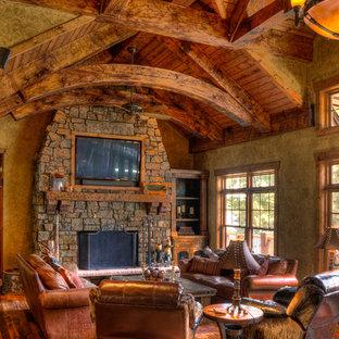 ミネアポリスの広いトラディショナルスタイルのおしゃれなオープンリビング (ベージュの壁、無垢フローリング、標準型暖炉、石材の暖炉まわり、埋込式メディアウォール、茶色い床) の写真