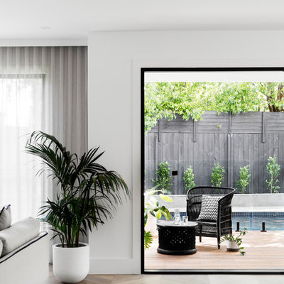 Trendy open concept medium tone wood floor and brown floor family room photo in Melbourne with white walls, a standard fireplace, a brick fireplace and a wall-mounted tv