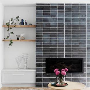 メルボルンのコンテンポラリースタイルのおしゃれなオープンリビング (白い壁、無垢フローリング、標準型暖炉、レンガの暖炉まわり、壁掛け型テレビ、茶色い床) の写真