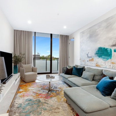 Example of a trendy medium tone wood floor and brown floor family room design in Melbourne with white walls and a tv stand