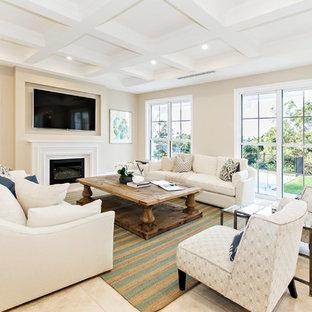 Imagen de sala de estar cerrada, clásica, con paredes beige, chimenea tradicional, marco de chimenea de yeso, televisor colgado en la pared y suelo beige