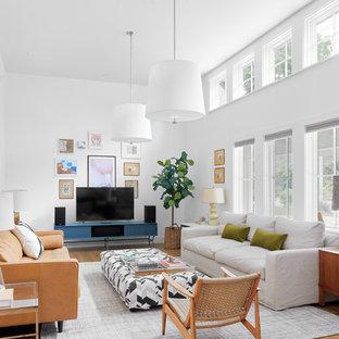 Imagen de sala de estar campestre con paredes blancas, suelo de madera clara y televisor independiente