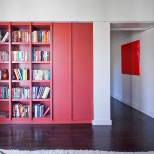 Exemple d'une grande salle de séjour avec une bibliothèque ou un coin lecture tendance fermée avec un mur blanc, un sol en bois foncé, aucune cheminée et aucun téléviseur.