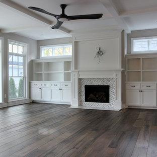 Foto de sala de estar abierta, de estilo americano, grande, con paredes grises, chimenea tradicional, marco de chimenea de baldosas y/o azulejos, televisor colgado en la pared, suelo marrón y suelo de madera oscura